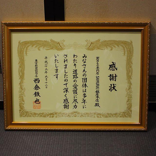 店舗前の花壇の清掃活動が認められ東京都建設局から道路功労者建設局長賞をいただきました。時計の裏にプレートがあります。これからも花壇を綺麗に維持していきたいと思います。