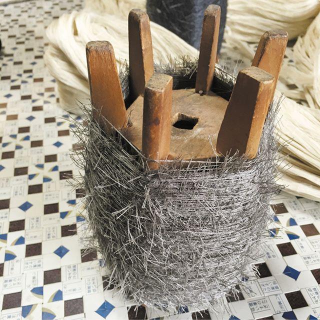 .米沢の職人さんが見せてくださいました。米沢は糸巻きのかたちもよく見かける4本ではなく、6本。独特の美しさがあり、モノ好きの心がくすぐられます。(実は、ピースの箱で織られたお手製のテーブルマットもすごく心惹かれました).巻かれているのは「髭紬ひげつむぎ」に使われる絹糸。うしろに写っている生糸を染めてから、糸全体に無数の髭をつくります。この髭が経糸に潰されないように、ひとつひとつ職人の手作業で引き出しながら織り上げる「髭紬」.「めんどうなんだよな〜。でも、カッコイイ帯ができるんですよ(笑)」と人懐っこい笑顔で話してくださいました。ただいまSAMURAI銀座本店には、髭紬の帯が入荷しております。数量限定ですので、気になったらぜひお早めにお店へお越しください。.#samurai #竹股織物 #たけぜん #米沢織 #米沢帯 #裂織り #髭 #角帯 #着物 #男着物 #きもの #夏きもの #ゆかた #浴衣